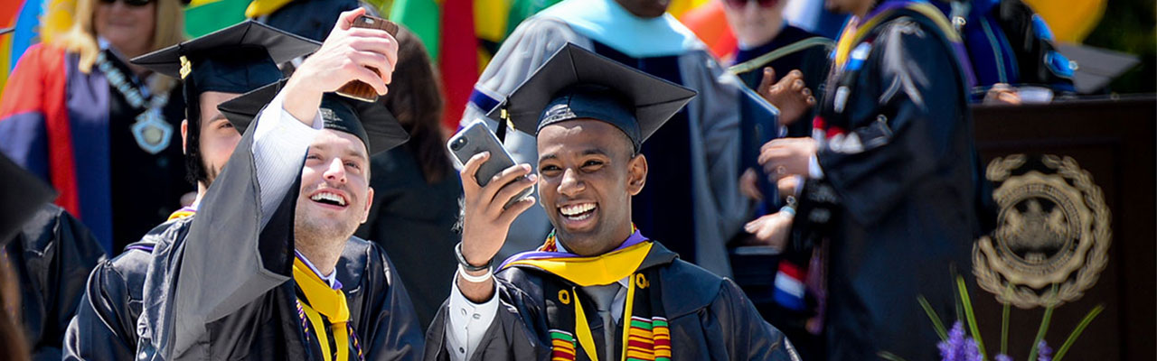 Two male students taking a selfie at graduation