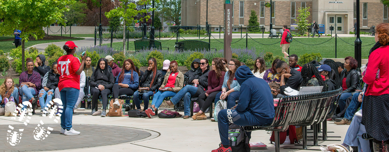 RUCCAS students outside on West Chester University's campus listening to speaker