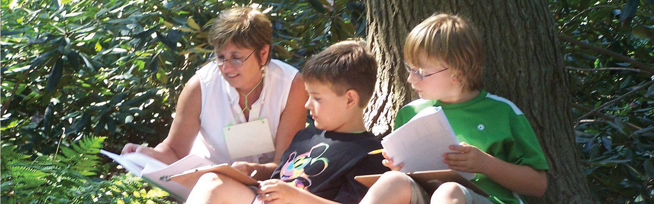 Teacher reading to two boys in front of tree