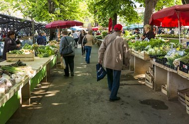 people shopping at an outdoor farmer's market