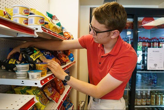 WCU student stocks the shelf at Ram Shop