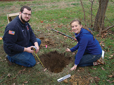 Male and female student measuring a hole in the ground