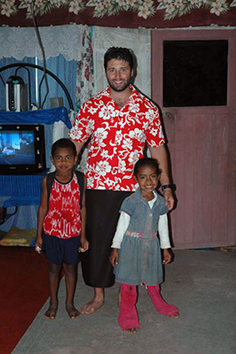 Anthropology graduate standing with two small children inside a house