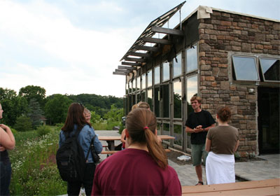 students and a teacher in front of a passive solar building