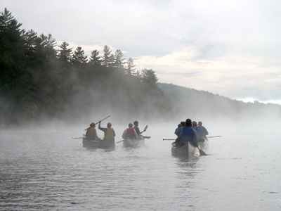 misty image of people canoeing on an Adirondack lake