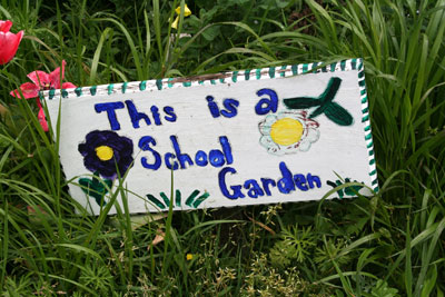 sign in the grass that says This is a school garden